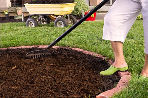 kaw-valley-prepare-yard-for-winter-woman-raking-mulch.jpg